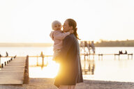 Germany, Bavaria, Herrsching, mother carrying daughter at the lakeshore at sunset - DIGF06748