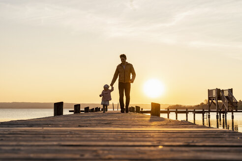 Germany, Bavaria, Herrsching, father and daughter walking on jetty at sunset - DIGF06751