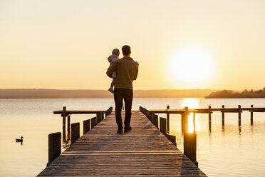 Germany, Bavaria, Herrsching, father carrying daughter on jetty at sunset - DIGF06754