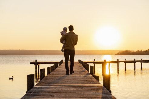 Deutschland, Herrsching, Vater 41 Jahre und Tochter 2 Jahre laufen zusammen auf einem Steg am See, Sonnenuntergang - DIGF06754