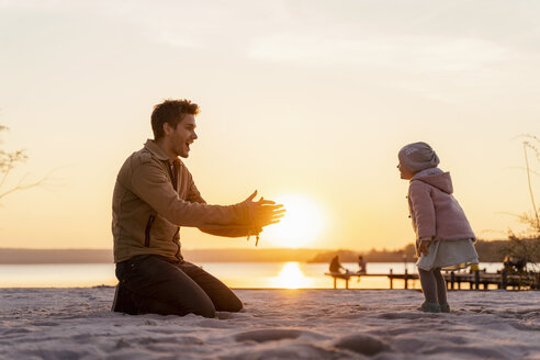 Germany, Bavaria, Herrsching, father and daughter playing on the beach at sunset - DIGF06757