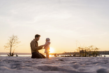 Germany, Bavaria, Herrsching, father and daughter playing on the beach at sunset - DIGF06760