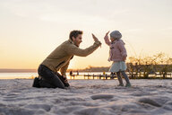 Germany, Bavaria, Herrsching, father and daughter playing on the beach at sunset - DIGF06763