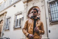 Italy, Florence, portrait of bearded man wearing sunglasses and light brown leather jacket - FBAF00366