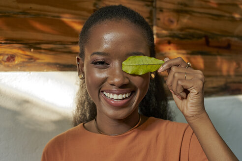 Portrait of happy young woman holding a leaf - VEGF00019