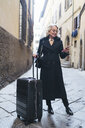 Mature businesswoman wearing black coat standing in an alley with rolling suitcase looking at cell phone - FBAF00384
