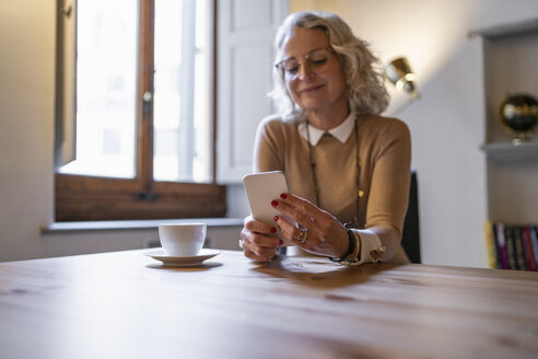 Mature businesswoman sitting at table with cup of coffee using smartphone - FBAF00390