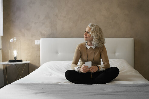 Mature businesswoman sitting on bed with mobile phone looking out of window - FBAF00399
