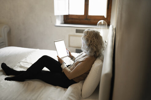 Mature businesswoman sitting on bed looking at digital tablet - FBAF00408