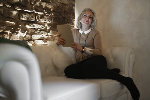 Portrait of happy mature businesswoman sitting on couch with digital tablet - FBAF00411