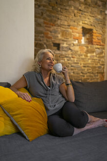 Happy mature woman relaxing on couch with cup of coffee - FBAF00429