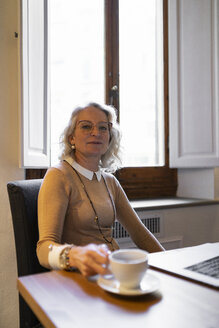 Portrait of content mature businesswoman sitting at table with laptop and cup of coffee - FBAF00432