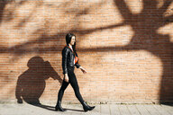 Young woman with a red bag walking in front of a brick wall and a shadow of tree - JRFF03083