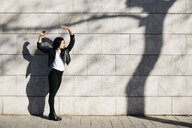 Young woman making shadows on a white wall with a shadow of a tree - JRFF03092