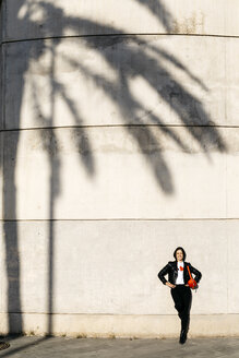 Happy young woman with a red hip bag resting on a wall with the shadow of a palm tree. - JRFF03098