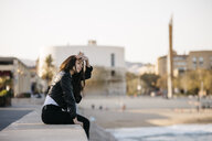 Young woman sitting on a wall - JRFF03116