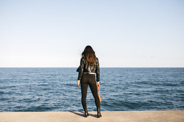 Rear view of a fashionable brunette woman looking at the sea - JRFF03125