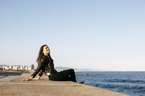 Young woman sitting on the wall at harbour - JRFF03131