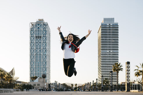 Spain, Barcelona, Young woman jumping, high-rise buildings in the background - JRFF03134