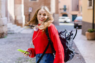 Young woman wearing red pullover, headphones and holding smartphone - GIOF06296