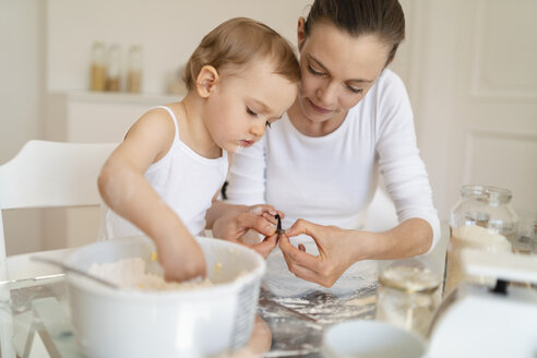 Mother and little daughter making a cake together in kitchen at home - DIGF06771