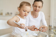 Mother and little daughter making a cake together in kitchen at home - DIGF06774