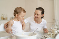 Mother and little daughter making a cake together in kitchen at home - DIGF06777