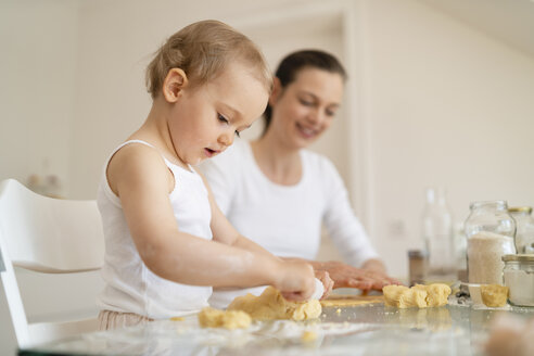 Mother and little daughter with dough roll making a cake together in kitchen at home - DIGF06783
