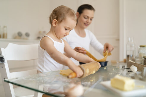 Mother and little daughter with dough roll making a cake together in kitchen at home - DIGF06786