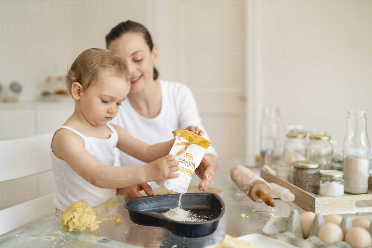 Mother and little daughter making a cake together in kitchen at home - DIGF06789 - Daniel Ingold/Westend61