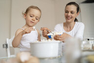 Mother and little daughter making a cake together in kitchen at home - DIGF06792