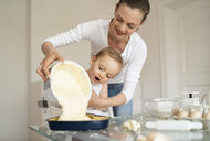 Mother and little daughter making a cake together pouring batter into baking pan - DIGF06795