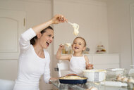 Happy mother and little daughter making a cake together in kitchen at home - DIGF06798