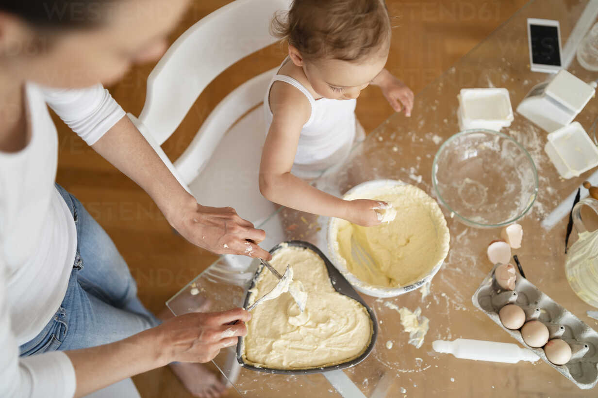 Top view of mother and little daughter making a cake together in kitchen at home - DIGF06801 - Daniel Ingold/Westend61