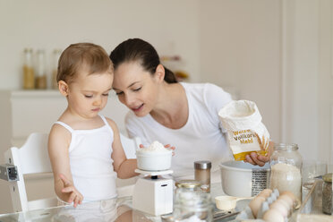 Mother and little daughter making a cake together in kitchen at home weighing flour - DIGF06804