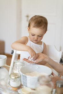 Mother and little daughter making a cake together in kitchen at home - DIGF06807