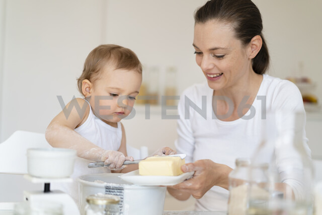 Mother and little daughter making a cake together in kitchen at home - DIGF06810 - Daniel Ingold/Westend61