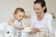 Mother and little daughter making a cake together in kitchen at home - DIGF06810