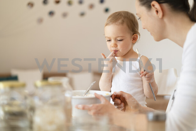 Mother and little daughter making a cake together in kitchen at home - DIGF06813 - Daniel Ingold/Westend61