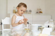 Girl making a cake in kitchen at home cracking an egg - DIGF06816