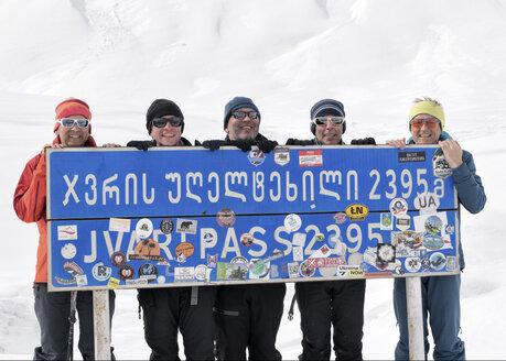Georgia, Caucasus, Gudauri, portrait of happy ski tourers holding a sign - ALRF01482