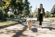 Happy woman going walkies in city park with her Labrador Retriever - JRFF03143
