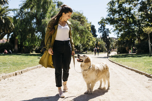 Happy woman going walkies in city park with her Labrador Retriever - JRFF03146