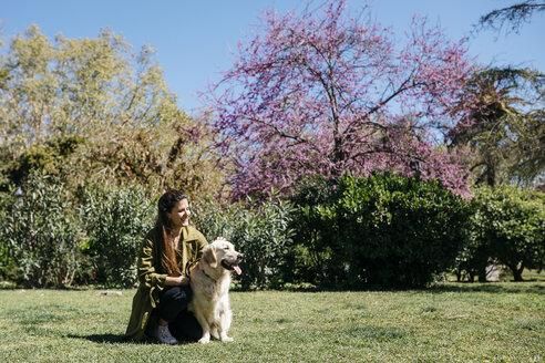 Happy woman stroking her Labrador Retriever on meadow in city park - JRFF03149