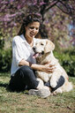 Happy woman sitting on meadow in city park with her Labrador Retriever - JRFF03152