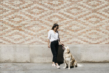 Happy woman stroking her Labrador Retriever in front of patterned brick wall - JRFF03155
