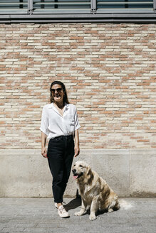Laughing woman standing besides her Labrador Retriever in front of patterned brick wall - JRFF03158