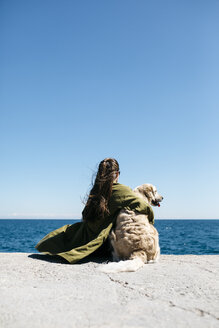Back view of woman sitting besides her Labrador Retriever at quay looking at horizon - JRFF03161