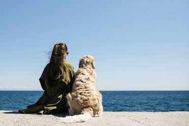 Back view of woman sitting besides her Labrador Retriever at quay looking to the sea - JRFF03164