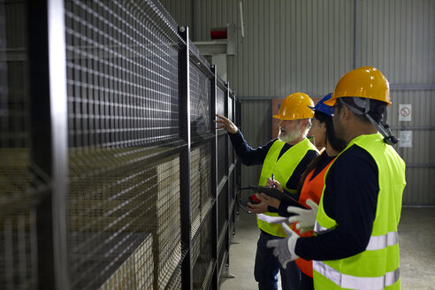 Workers standing at grid in factory talking - ZEDF02232